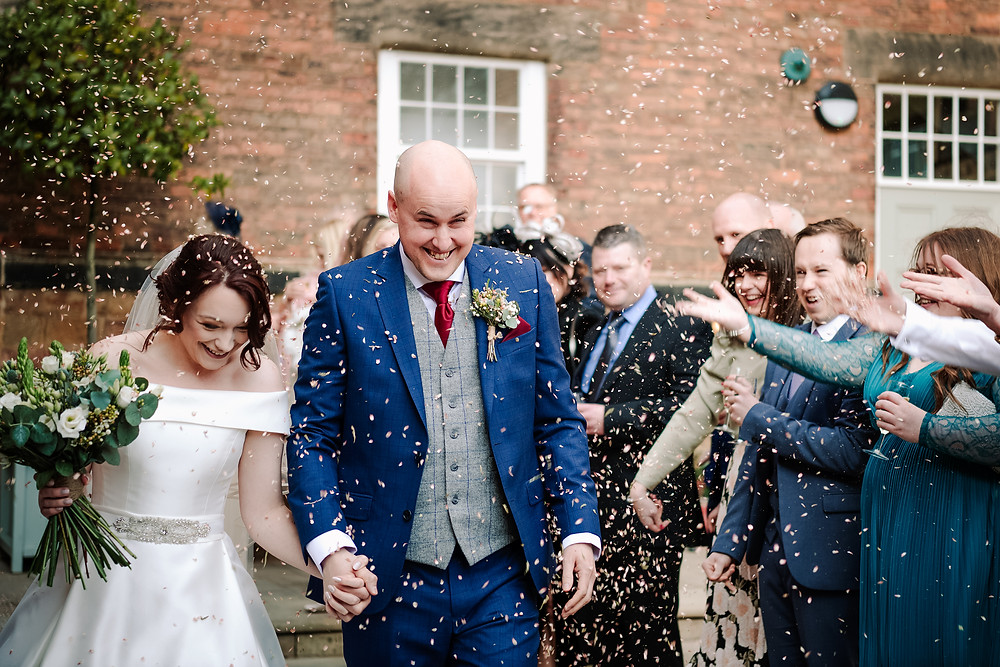 Wedding Photographer Solihull, Birmingham, couple holding hands walking through the confetti at the west mill derby