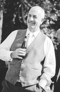 Hampton Manor Wedding photographer West Midlands, grooms father having a laugh at a wedding, candid photograph