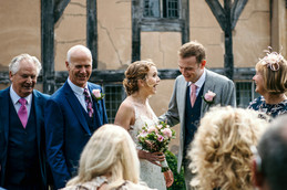 Photography wedding Birmingham, the bride & groom laughing with their wedding guests at the lord leycester warwick wedding venue