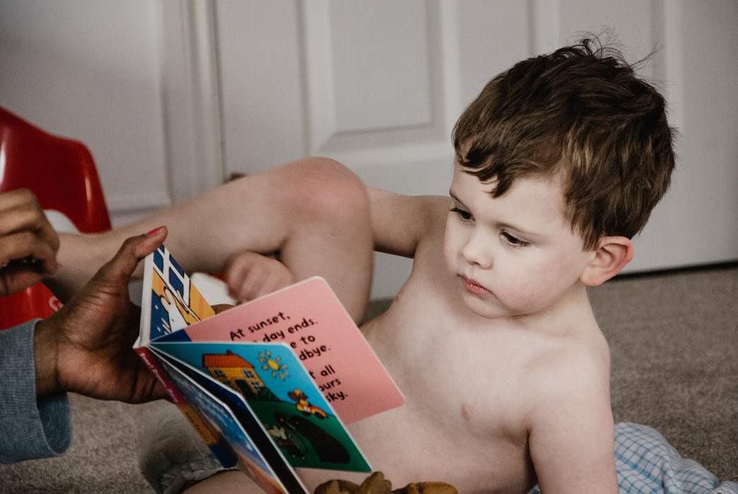 Family Photographer Solihull, lifestyle photo shoot of a little boy reading with his carer, autism photo shoot