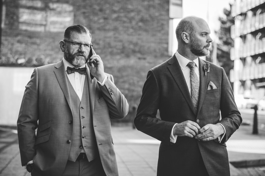 Civil ceremony wedding photographer Birmingham, the two grooms standing on the street making a call before their wedding, black & white candid photograph,