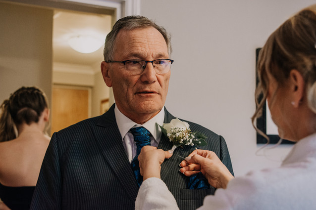 Wedding Photography Solihull, the father of the bride having his buttonhole flower put on before his daughters wedding at the Westmead hotel Birmingham