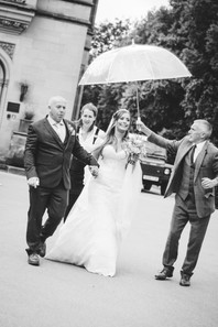 Hampton Manor Photographer Solihull, Bride with her dad & assistants walking with an umbrella towards the camera, fun wedding photography