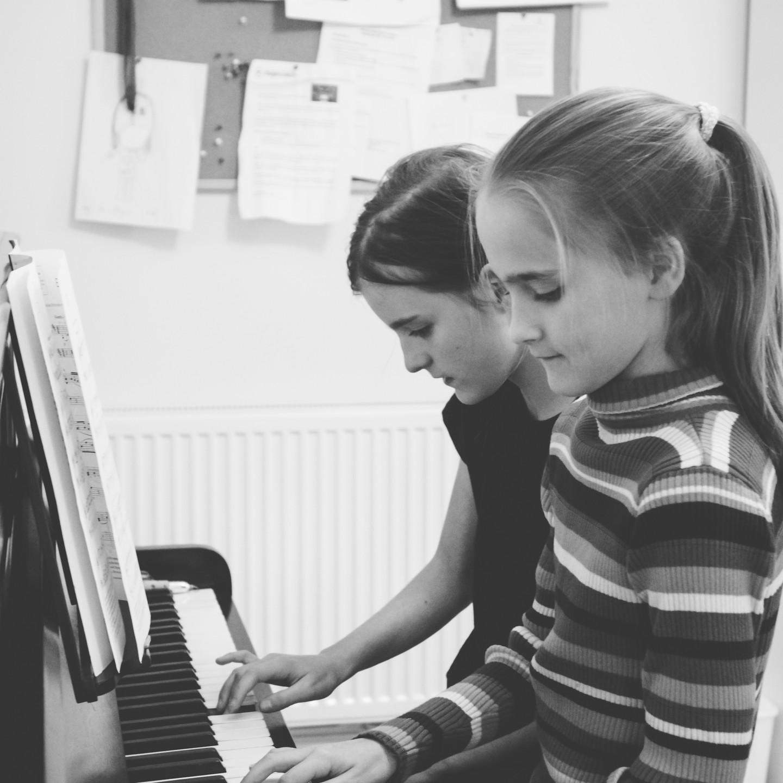 Family lifestyle photographer Birmingham, two girls playing the piano, black & white image