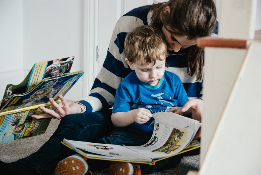 Photographer for children with autism, little boy looking at books with his carer