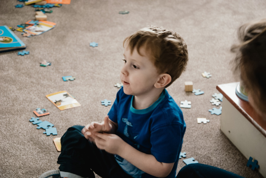 Lifestyle Family Photographer Birmingham, photographing children with aurism in their home, natural photograph of a boy playing with a jigsaw