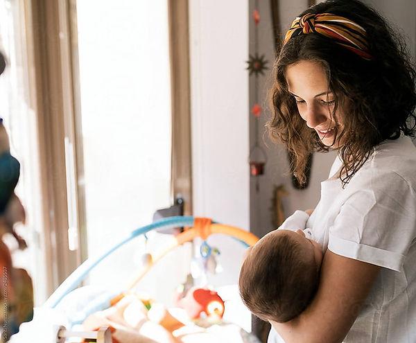 postpartum doula holds newborn inthe nursery