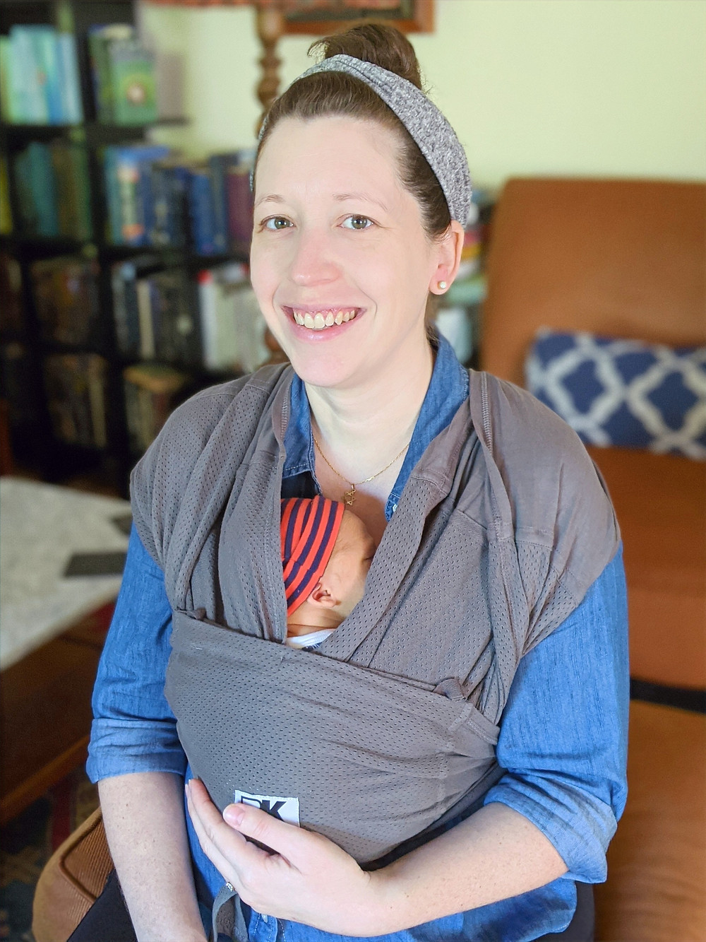 postpartum doula helps mom wrap baby in the carrier