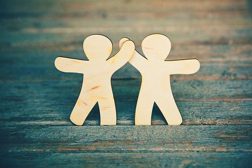 Wooden little men holding hands on wooden boards background. Symbol of friendship, love an