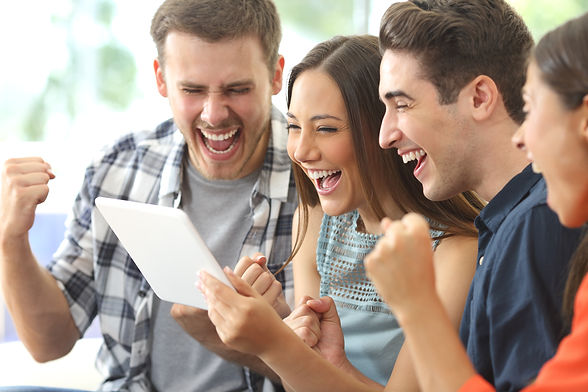 Excited group of four friends viewing media content on line from a tablet in a house inter