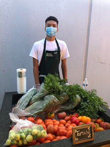 Black man with mask standing in front of vegetables