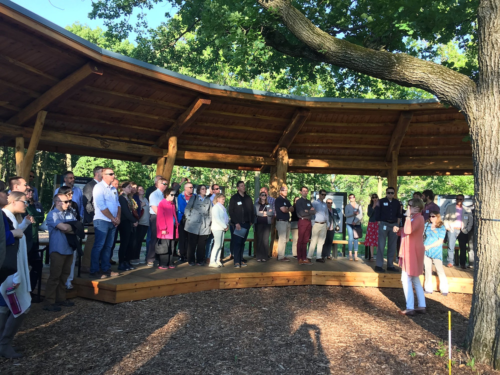 people standing under a wood circular canopy listening to speaker