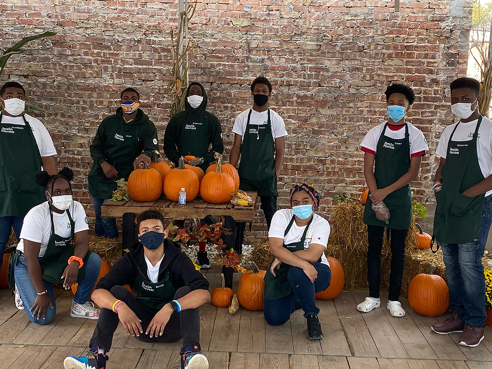 group photo of people wearing black and white clothes with pumpkins displayed around them