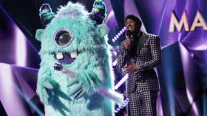 a stage with purple background. someone is singing into a microphone with someone in a monster costume next to the singer.
