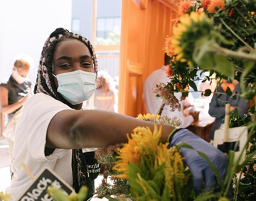 Black woman with mask on attending to flowers and foliage