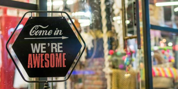 sign in store window that says Come in We're Awesome