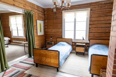 Olohuoneen viereinen makuuhuone, johon tuo lämpöä tiilinen takka.