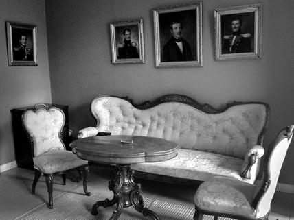 Kartanon alkuperäinen sohvakalusto ja Maria Nordmannin setien muotokuvat.
