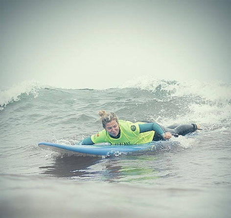 Woman paddle to catch a wave in a surf lesson with Waterlost Surfschool in peniche, Portugal