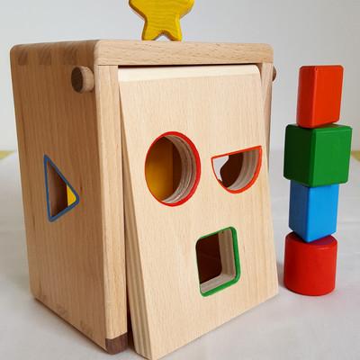 Jouet en bois fabriqué en france (pays de la loire) : boite a formes Clin d'oeil. La boite à formes est un jeu d'éveil pour découvrir et apprendre à distinguer les formes et les couleurs. La manipulation des pièces permet aussi de développer la dextérité de l'enfant et sa motricité fine.  L'ensemble comprend 5 pièces à manipuler : un cylindre, un carré, une étoile, un prisme triangulaire et un demi-cylindre. Avec la disposition des ouvertures, la boite semble représenter une tête avec des oreilles, une bouche et des yeux qui font un clin d'oeil.    En bois de hêtre &contreplaqué de hêtre  Dimension : 16.5 cm x 14 cm x 10 cm Jeu conseillé à partir de 1 an    Fabriqué à la main, chaque modèle est unique.    Conforme aux normes européennes EN71-1 et EN71-3.