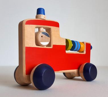 Jouet en bois : camion de pompier pour bébé. Lecamion de pompier est un jouet hochet à manipuler et un véhicule en boisà pousser.  Ce jouet d'éveil permet de stimulerplusieurs sens : - La vue, les couleurs vives attirent le regard - Le toucher : plusieurs contours et détails sont à découvrir et à manipuler (gyrophare, perles, tête du pompier...) - L'ouïe : à chaque mouvement, les perles s'entrechoquent et créent un petit cliquetis... &plus on secoue, plus c'est sonore !    Petit plus : la tête du pompier est mobile ( il peut donc regarder à droite, à gauche... et même derrière !).   Dimension : 17 cm x 11.5 cm Jouet en bois de tilleul  Dès la naissance    Fabriqué à la main, chaque modèle est unique. Conforme aux normes européennes EN71-1 et EN71-3.Fabriqué en France.