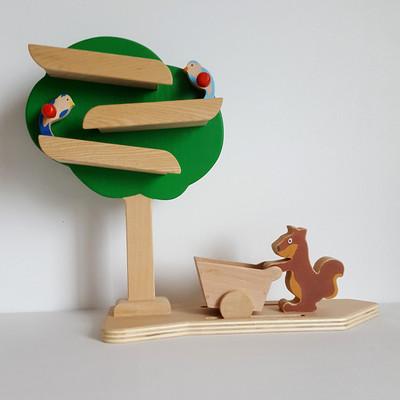 Circuit a billes. Le jeu du Pommier est un jeu d'observation qui permet de stimuler l'esprit logique et la concentration.  Avec ce circuit, l'enfants'amuse àplacer etàregarderles billes descendre. Les oiseauxrelancent la bille mais pour aider l'écureuilà ramasser des pommes, l'enfantdevra aussi penser à placer le chariot sur les rails ! et pour que la bille tombe directement dans le chariot, il faudra le placer au bon endroit !   Le jeu comprend un plateau avec l'arbre et ses 2 oiseaux, l'écureuil avec son chariot et 3 billes. Jouet en bois de hêtre, platane et contreplaqué de peuplier  Conseillé à partir de 3 ans      Conforme aux normes européennes EN71-1 et EN71-3. Fabrication artisanale française.