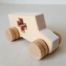 Jouet en bois : Ambulance blanche et rouge. Dans cette collection de véhicules en bois, 5 modèles : la voiture de course, la berline, la citadine, le camion et l'ambulance.  Ce sont de grandes voitures pour petites mains, entièrement faites en bois. Alors en route !    En bois de hêtre ou tilleul  Conseillé à partirde 1 an  Les dimensions varient en fonction des modèles.  Exemplede dimensions - Voiture de course : 14.5 x 4.5 cm  - Berline : 12 x 6 cm- Camion: 13.5 x 7.5 cm    Si le modèle souhaité n'est pas en stock, vous pouvez le commander, choisir la couleur et le faire personnaliser avec l'ajout d'un prénom.    Conforme aux normes européennes EN71-1 et EN71-3.Jouet fabriqué et peint à la main en France.