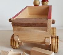 Jouet en bois fabriqué en France : le camion avec benne basculante. Ce camion est un grand jouet à pousser et un jouet à tirer. La ficelle étant amovible, vous pouvez choisir. Le véhicule est accompagné de 2 personnages en bois qui peuvent s'installer à l'avant du véhicule. Quand ils sont arrivés à destination, l'enfant peut commencer à vider le chargement. Pour cela, rien de plus simple. Il suffit de soulever la benne basculante et d'ouvrir la portière arrière. 10 pièces en bois glisseront alors au sol.    Petit plus- Un jeu de réflexion permet de stimuler la mémoire et l'esprit logique des plus grands.Comme pour un puzzle ou un casse-tête, l'enfant doit réussir à disposer les 10 éléments sur un même niveau. Ainsi, tout le stock peut êtredéchargépar la portière arrière.  Camion en bois de noyer, hêtre et frêne. Dimension du camion : 25 cm x 11,5 cm x 15 cm Hauteur des personnages en bois : 6.5 cm Exemplaire unique !    Conforme aux normes européennes EN71-1 et EN71-3.