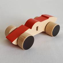 Jouet en bois : voiture de course rouge. Dans cette collection de véhicules en bois, 5 modèles : la voiture de course, la berline, la citadine, le camion et l'ambulance.  Ce sont de grandes voitures pour petites mains, entièrement faites en bois. Alors en route !    En bois de hêtre ou tilleul  Conseillé à partirde 1 an  Les dimensions varient en fonction des modèles.  Exemplede dimensions - Voiture de course : 14.5 x 4.5 cm  - Berline : 12 x 6 cm- Camion: 13.5 x 7.5 cm    Si le modèle souhaité n'est pas en stock, vous pouvez le commander, choisir la couleur et le faire personnaliser avec l'ajout d'un prénom.    Conforme aux normes européennes EN71-1 et EN71-3.Jouet fabriqué et peint à la main en France.