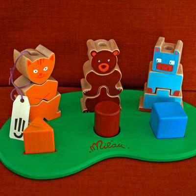 Le jeu des 3 copains permet de se familiariser avec les formes et les couleurs tout en s'amusant avec des petits animaux (un chat, un ours et une vache).  Chaque animal est associé à une forme (triangle, rond et carré). Ses contours sont donc dessinés en fonction de cette forme (lignes arrondies, droites...).  Sur le plateau, 3 tiges permettent d'empiler les pièces. L'enfant peut ainsi améliorer sa dextérité et sa motricité fine.     En bois de hêtre & contreplaqué de hêtre   Jeu conseillé à partir de 1 an    Fabriqué à la main, chaque modèle est unique. Les couleurs sont au choix et un prénom peut être ajouté sur le plateau.      Conforme aux normes européennes EN71-1 et EN71-3. Jouet artisanal 100% made in france (bois, peintures et vernis).