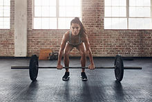Female performing deadlift exercise with
