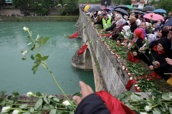 Bosnian Muslims toss 3,000 roses into the Drina River, each representing people killed in the 1992-95 war, in the eastern Bosnian town of Višegrad, on May 26, 2012 [File: AP/Amel Emric]