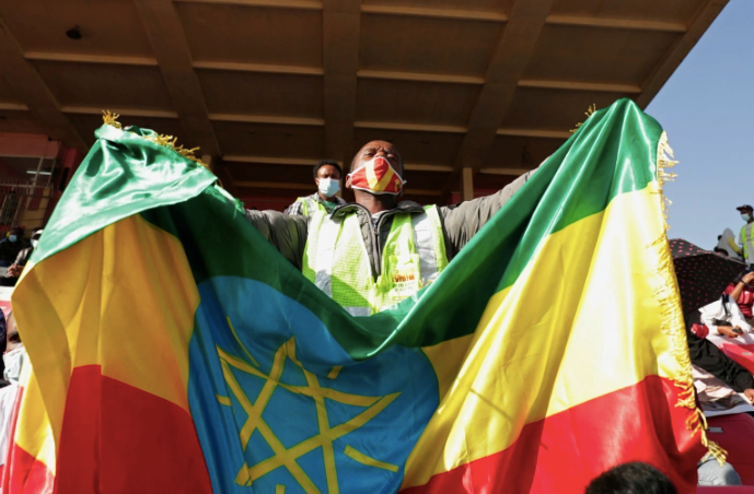 A volunteer holds an Ethiopian flag during a blood donation drive for the injured members of Ethiopia's military fighting against Tigray's special forces [Tiksa Negeri/Reuters]