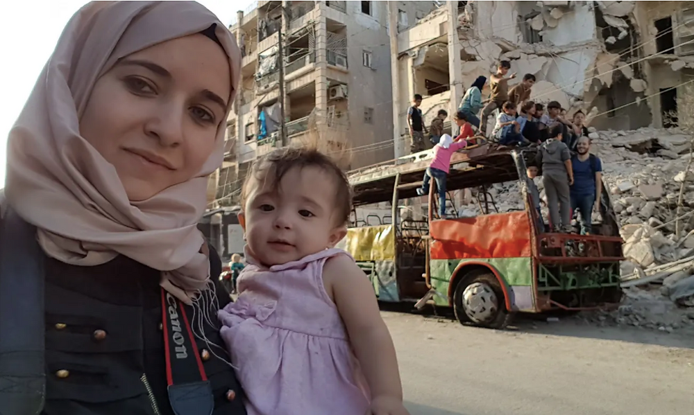 Al-Kateab and her daughter, Sama, in Aleppo in 2016, with the 'playground bus' behind them. Photograph: Waad Al-Kateab