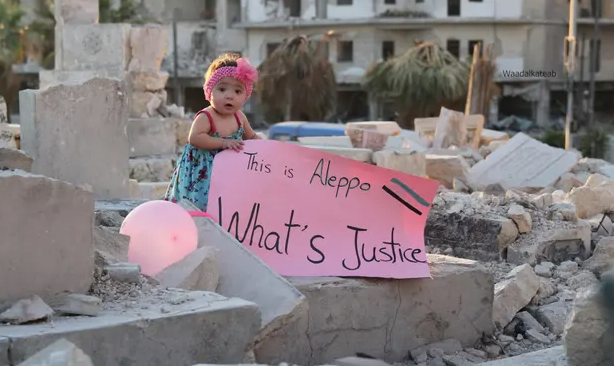 Sama at the end of the documentary holding a sign that formed al-Kateab's response to US presidential candidate Gary Johnson's remark, 'What's Aleppo?'