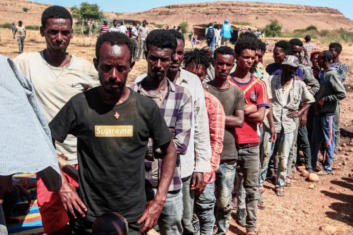 Ethiopian refugees fleeing fighting in Tigray queue to receive supplies at the Um Rakuba camp in Sudan's eastern Gadarif province [Ebrahim Hamid/AFP]