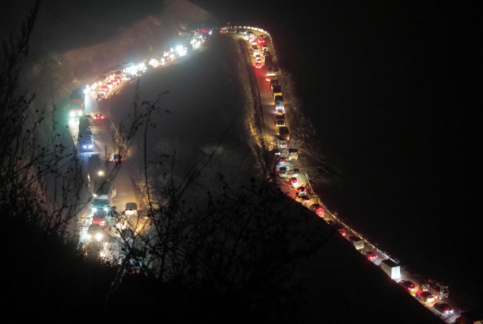 A backed-up line of cars and trucks stuck climbs along the road from Kalbajar on Saturday [Dmitry Lovetsky/AP]