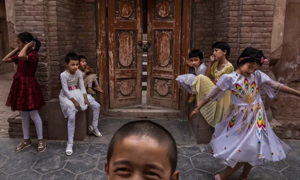 Uighur children sit outside a mosque in Kashgar in June 2017 after it was closed by Chinese authorities. Photograph: Kevin Frayer/Getty Images