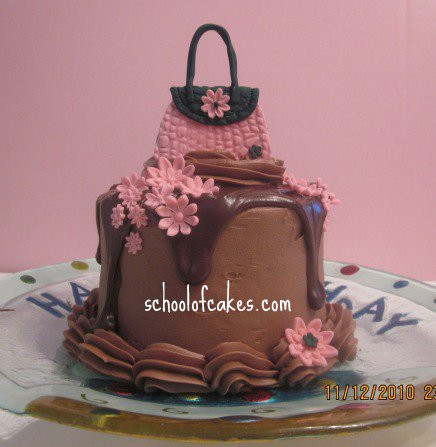 Chocolate buttercream cake with ganache drip around the side with small purse on top