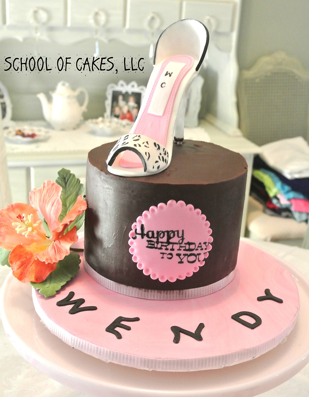 Chocolate Ganache covered cake decorated with a flower and a shoe on top