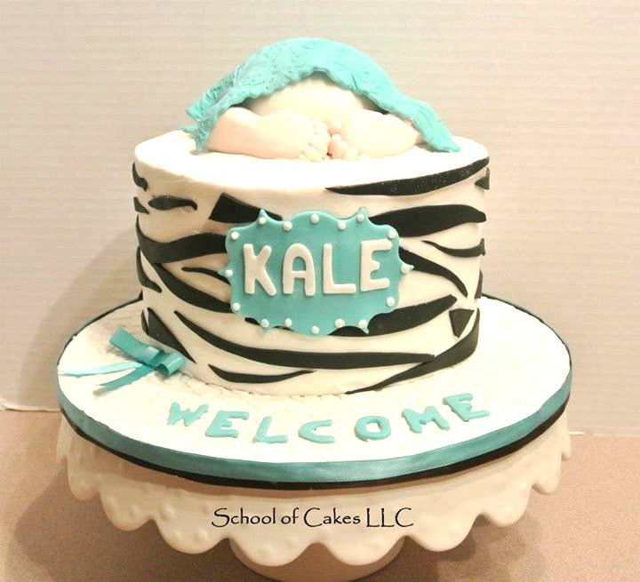 A zebra stipend cake with a baby on top with the name Kale and a covered cake board
