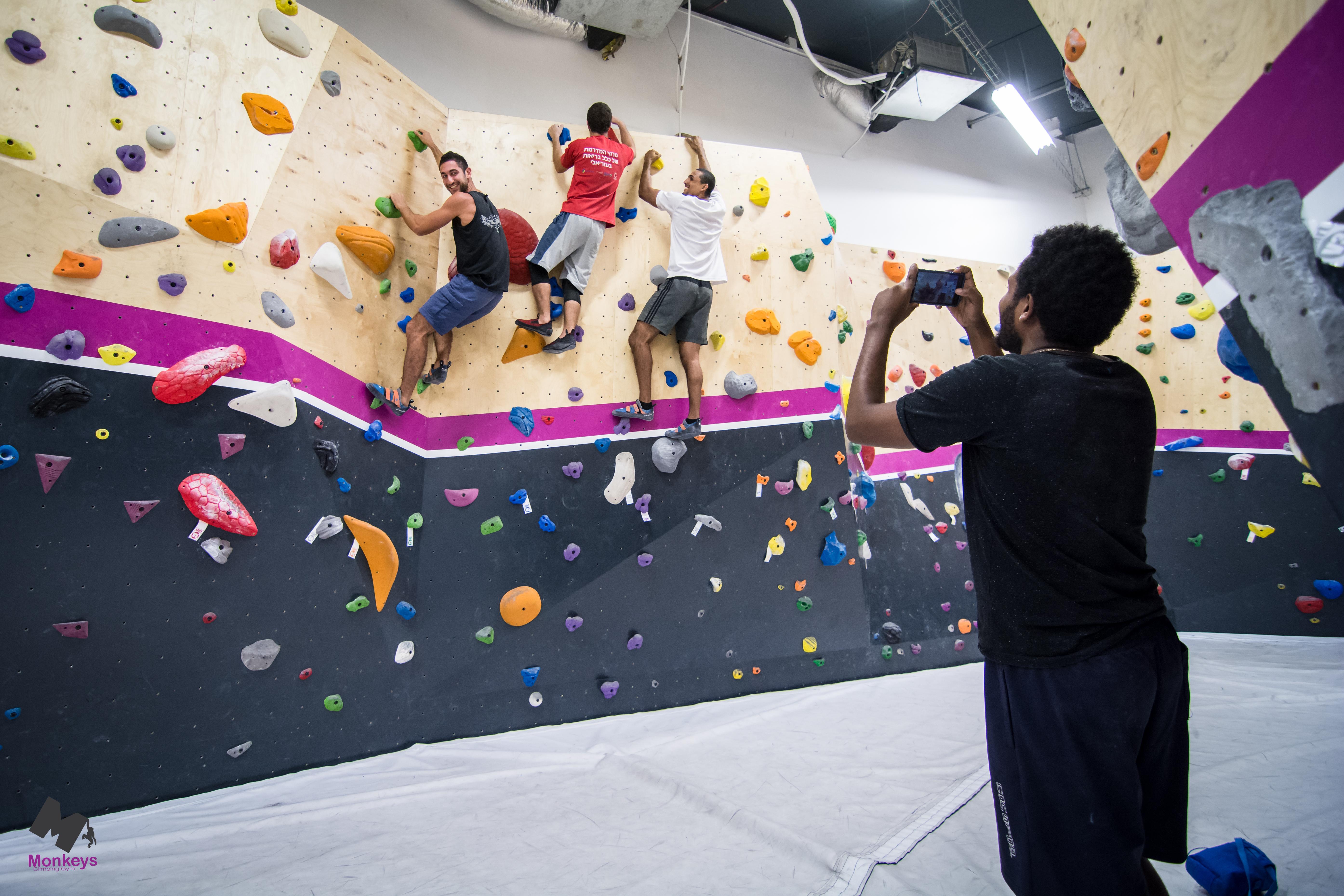 אדם מצלם שלושה מטפסים שעל הקיר טיפוס