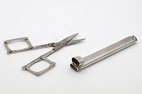 Silver case containing folding scissors