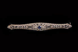Gold brooch of a tapered pierced foliate bar with square shaped sapphire flanked on either side by a brilliant cut diamond