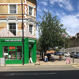 Image of a green shop front near a large tree