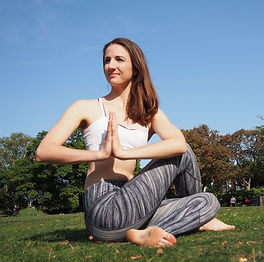 Photo of Sarah, the yoga instructor doing a seated pose in the park