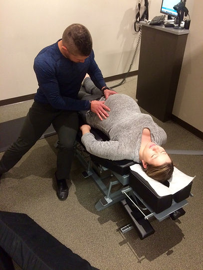 Chiropractic adjustment being given to a pregnant woman.