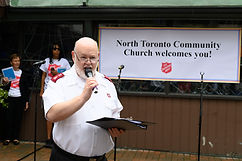 Ken Smith speaking into a mic infront of a welcome banner outdoors the church