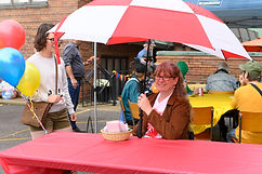 Female greeter sitting at a table under an umbrella.