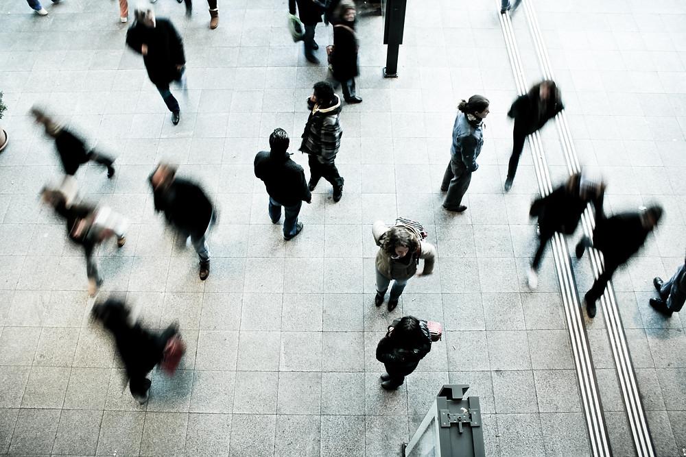 Pessoas de preto andando em um lugar cinza.